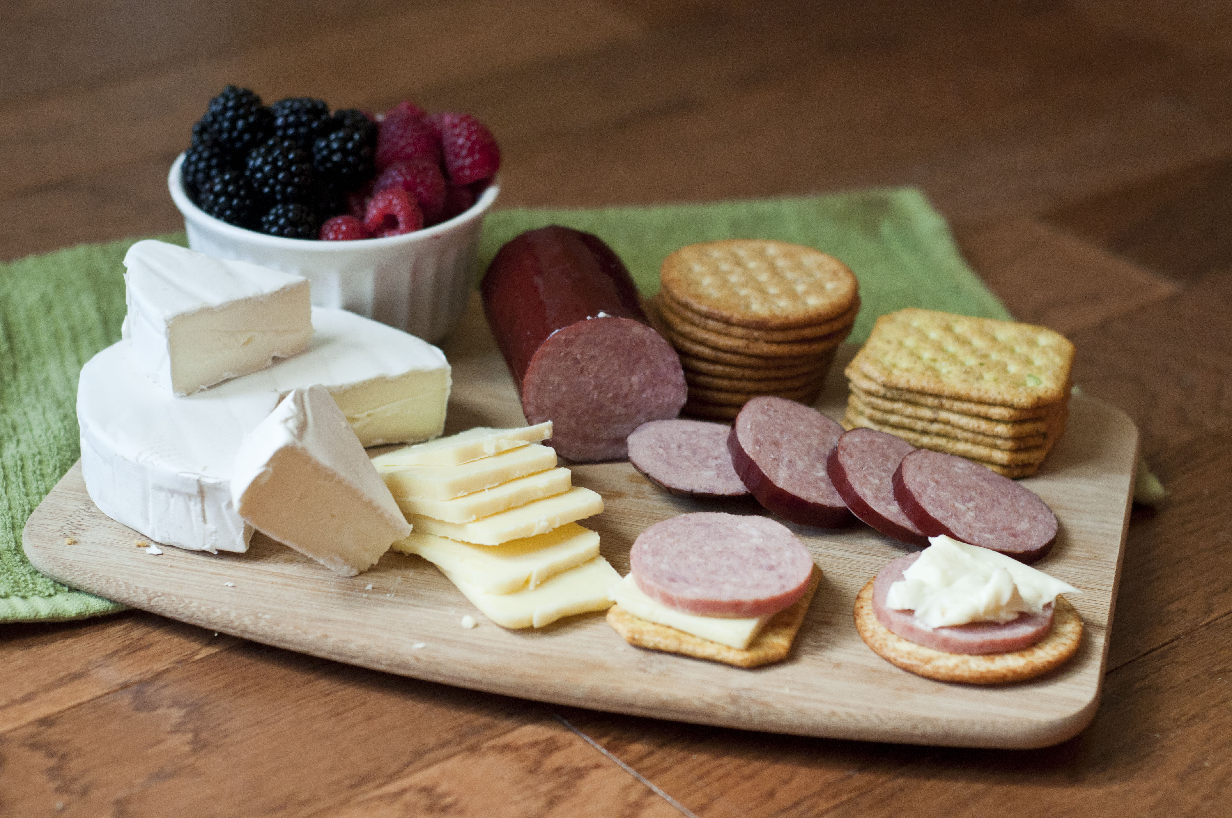 This photo is a colorful example of a Cheese Board appetizer using Petit Jean Summer Sausage. On this cheese board is summer sausage, brie, extra sharp aged white cheddar, crackers and berries.