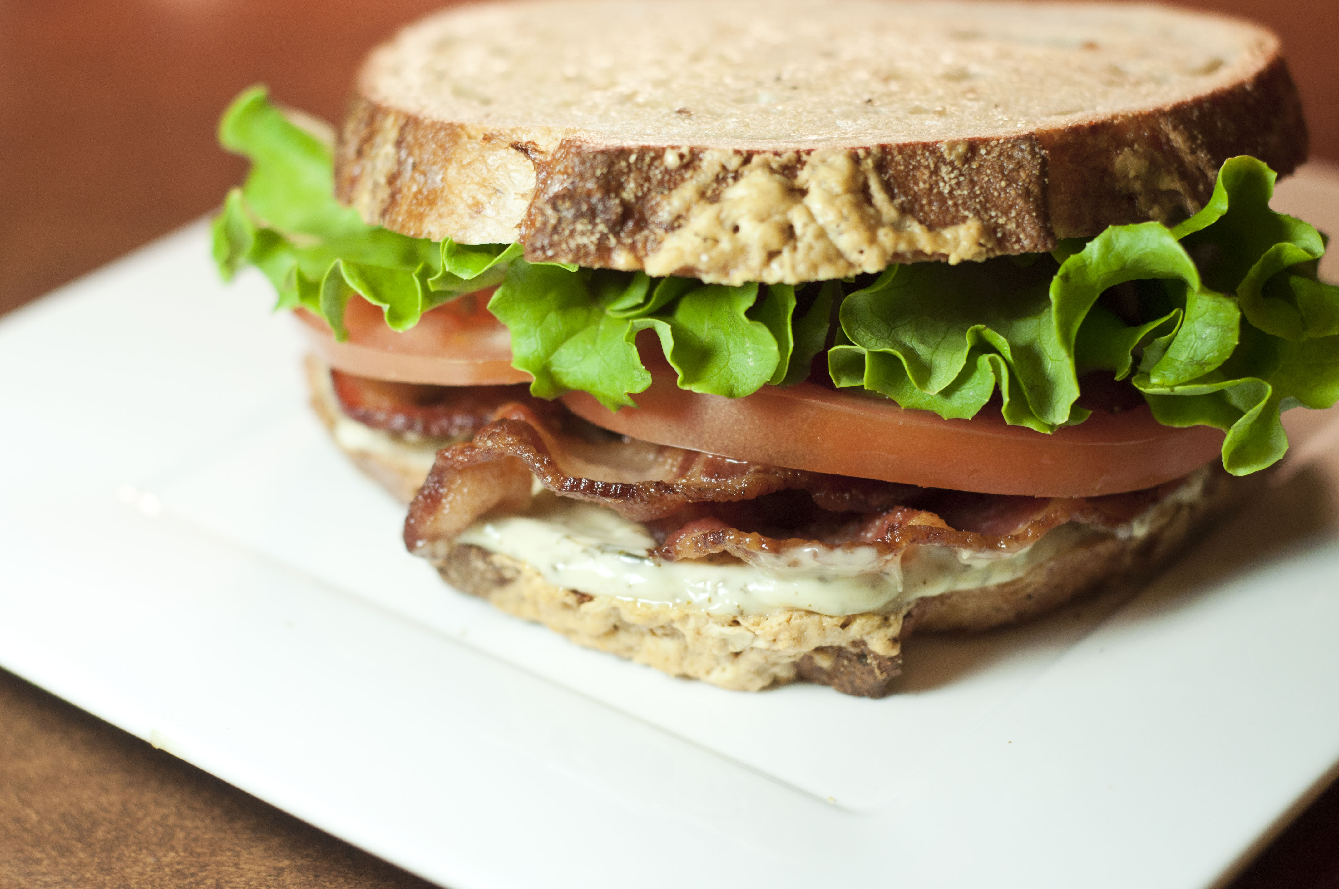 this picture is of a delicious BLT on artisan bread with pesto mayonnaise