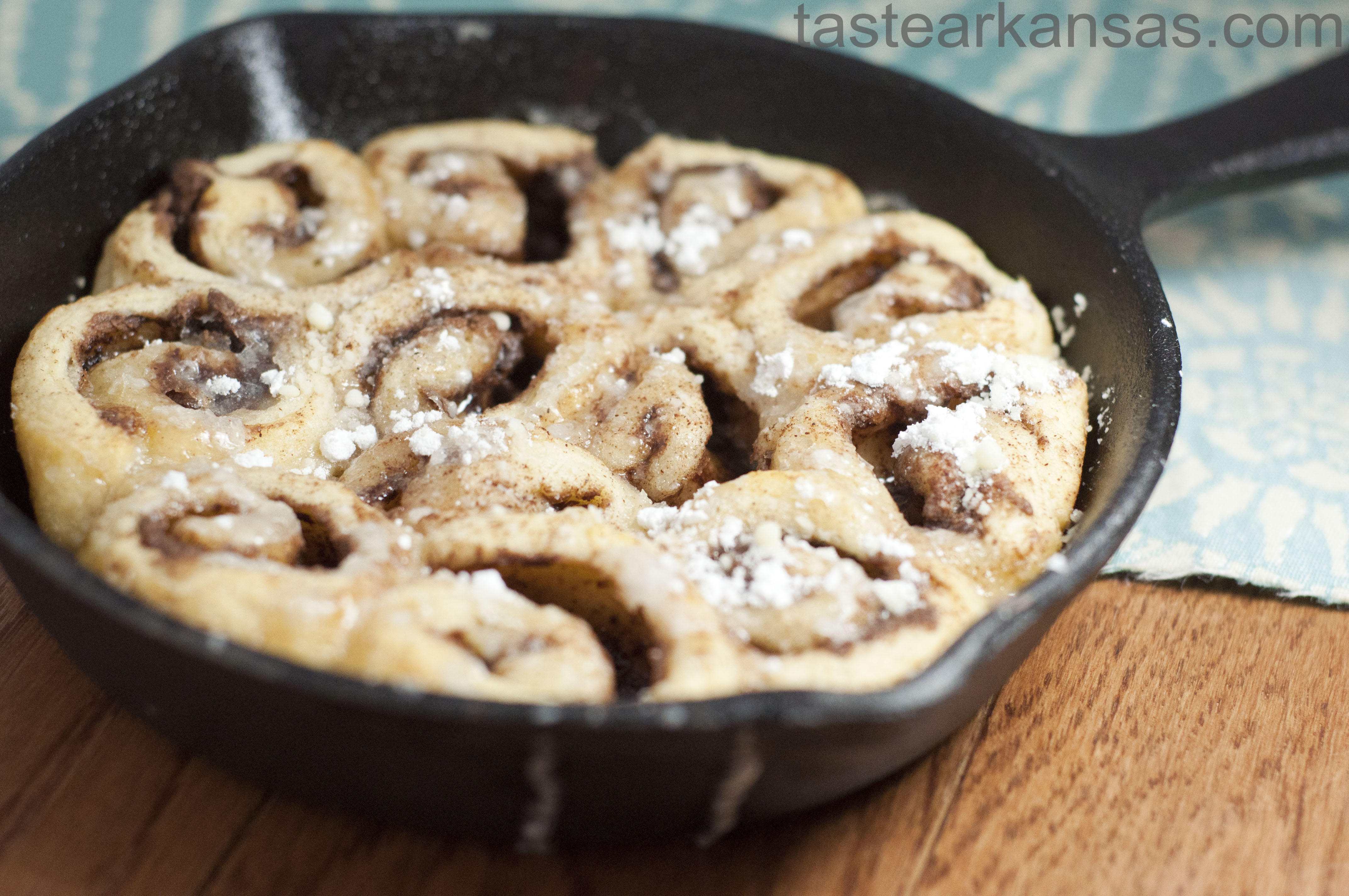 this image shows a cast iron skillet full of nutella cinnamon rolls