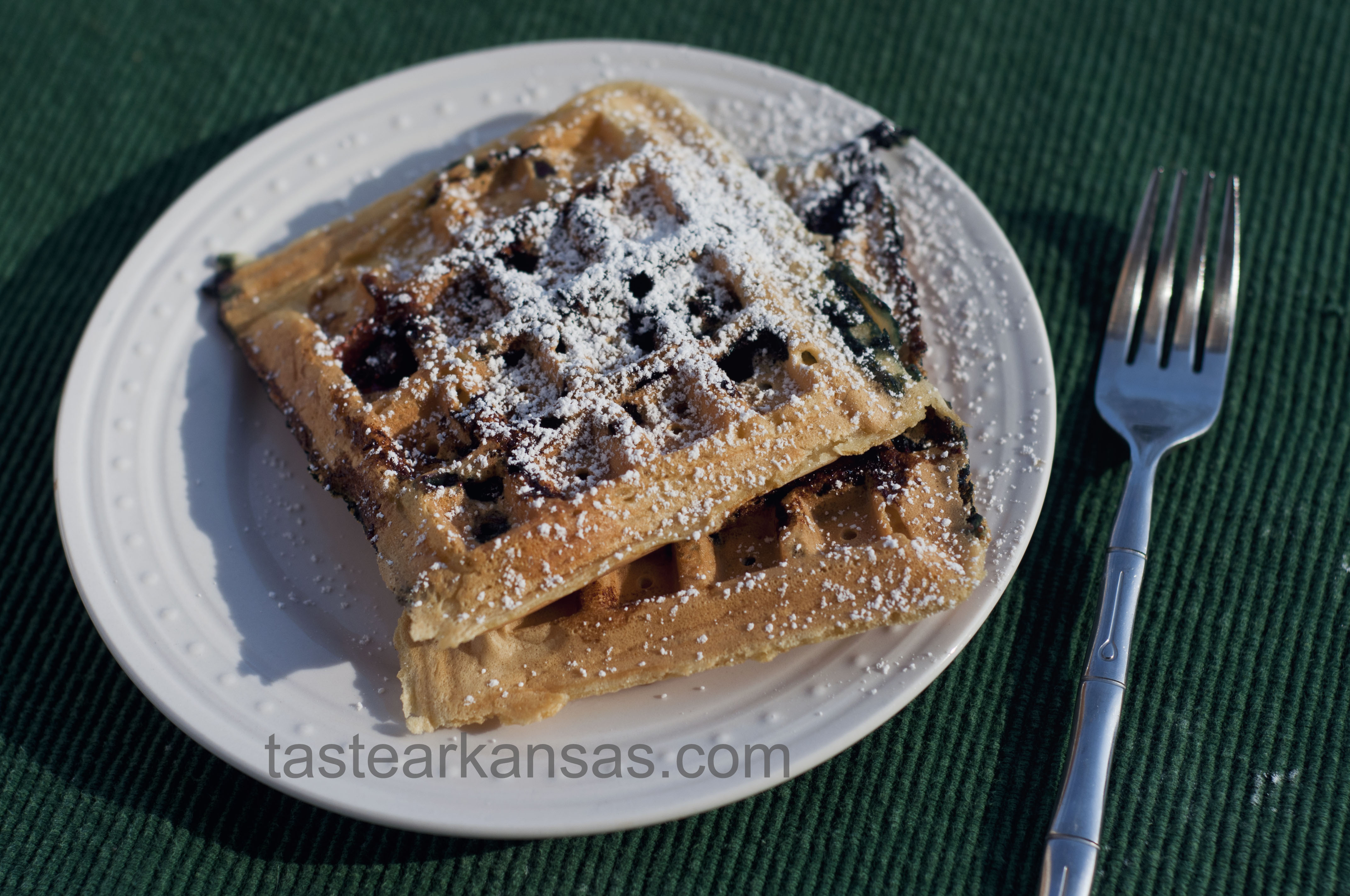 a warm plate of blueberry waffles with a dusting of powdered sugar